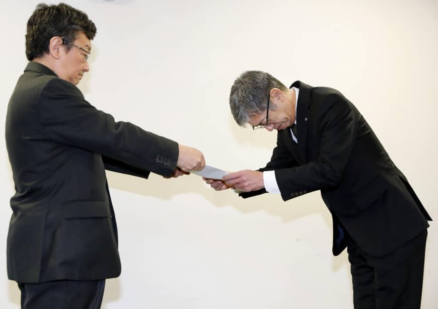 Japan Airlines Co. President Yuji Akasaka (right) receives a business improvement order at the transport ministry on Friday. Image via KYODO