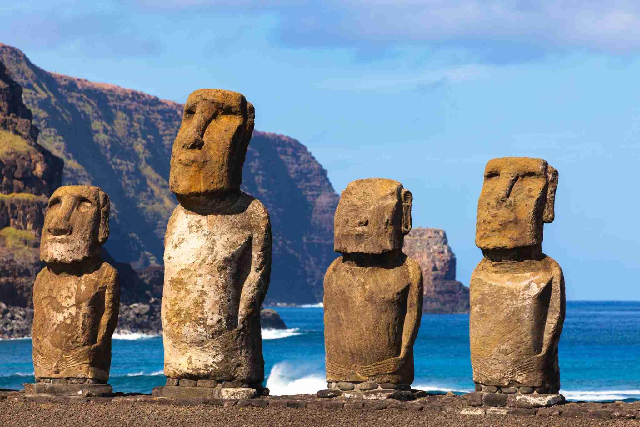 The Easter Island Moi at Ahu Tongariki - four moai, cliff, sky and blue sea.