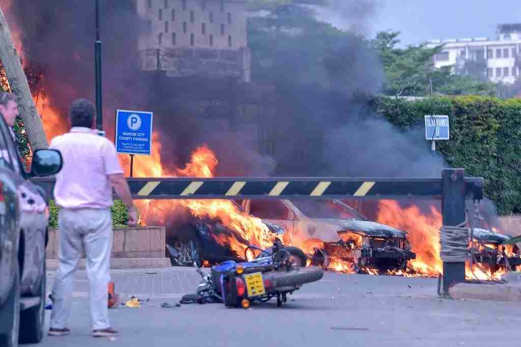Two men stand next to burning cars at the scene of an explosion at a hotel complex in Nairobi on January 15, 2019. - A blast at the DusitD2 compound, which includes a hotel and several office buildings housing international companies, was heard from AFP