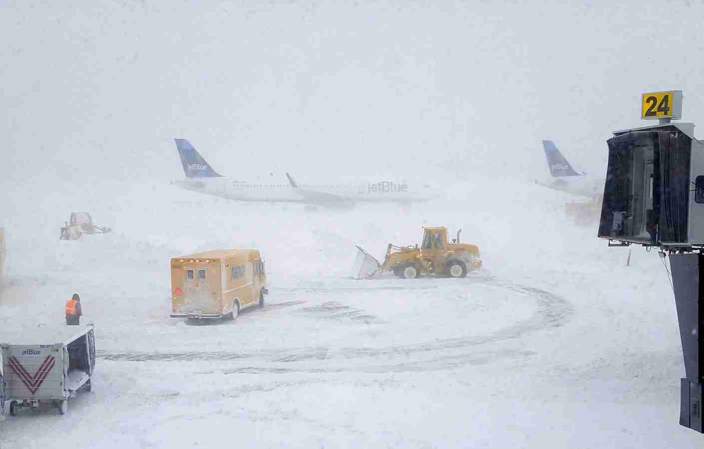 NEW YORK, NY - JANUARY 04:  Snow plows move snow as a JetBlue airplane waits outside terminal five at John F. Kennedy International Airport on January 4, 2018 in the Queens borough of New York City. A winter storm is traveling up the east coast of the United States dumping snow and creating blizzard like conditions in many areas. (Photo by Rebecca Butala How/Getty Images)