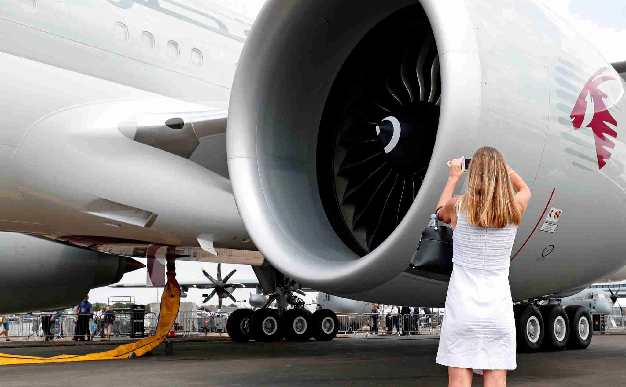A visitor photographs the General Electric GE90 engine of a Qatar Airways operated Boeing 777-3DZ passenger aircraft Farnborough Airshow, south west of London, on July 19, 2018. (Photo by Adrian DENNIS / AFP) (Photo credit should read ADRIAN DENNIS/AFP/Getty Images)