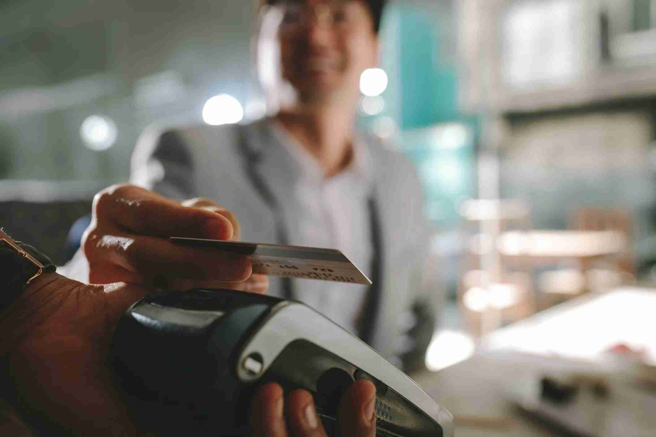 Close up of businessman paying with contactless credit card with nfc technology at restaurant. Focus on man holding his credit card above the card reading machine.
