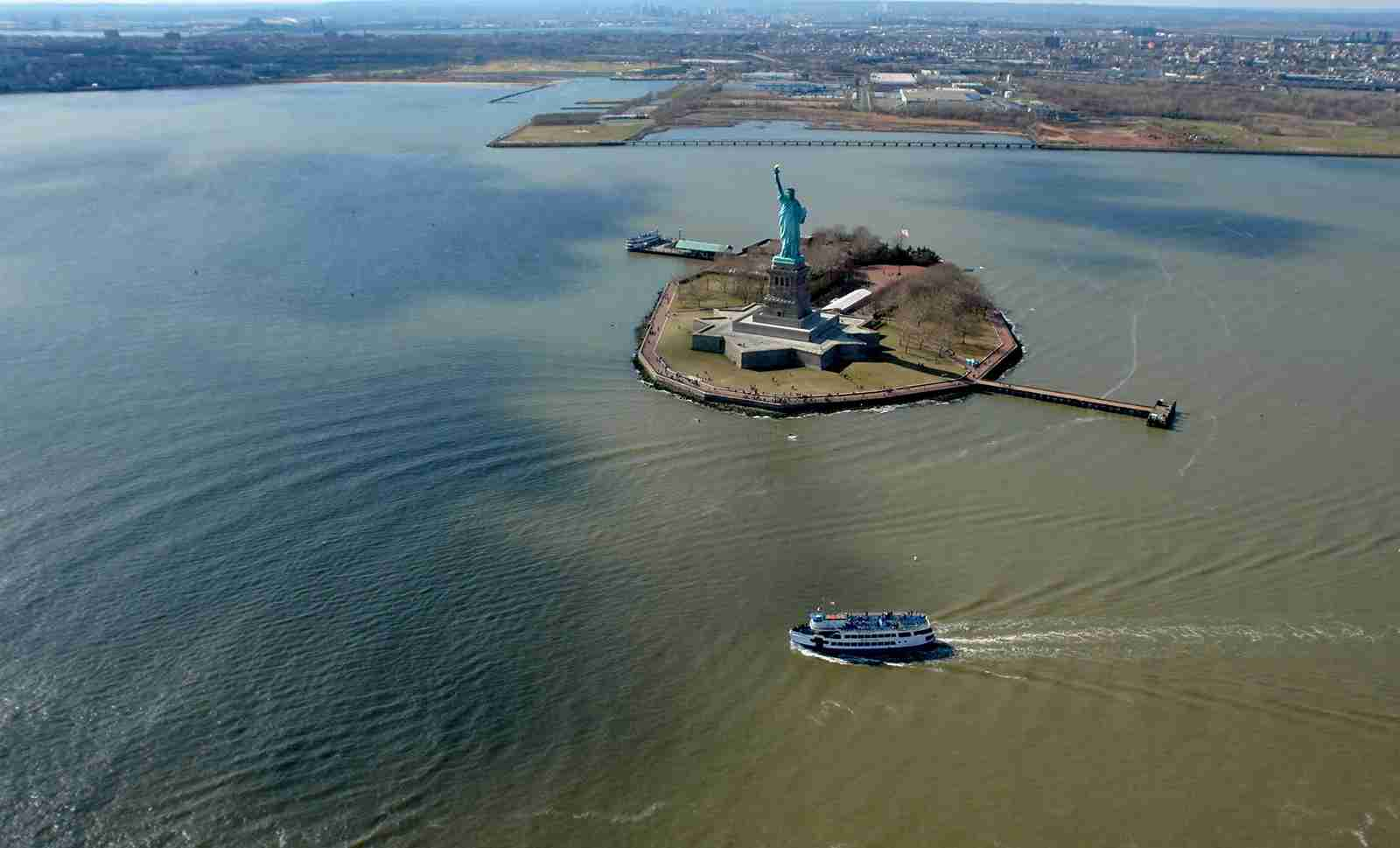 A cruise sailing past the Statue of Liberty. (Photo by steinphoto/Getty Images)