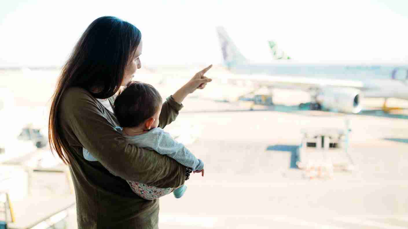 Mother holding a baby girl at the airport, pointing at the airplanes (Image by Westend61 / Getty Images)