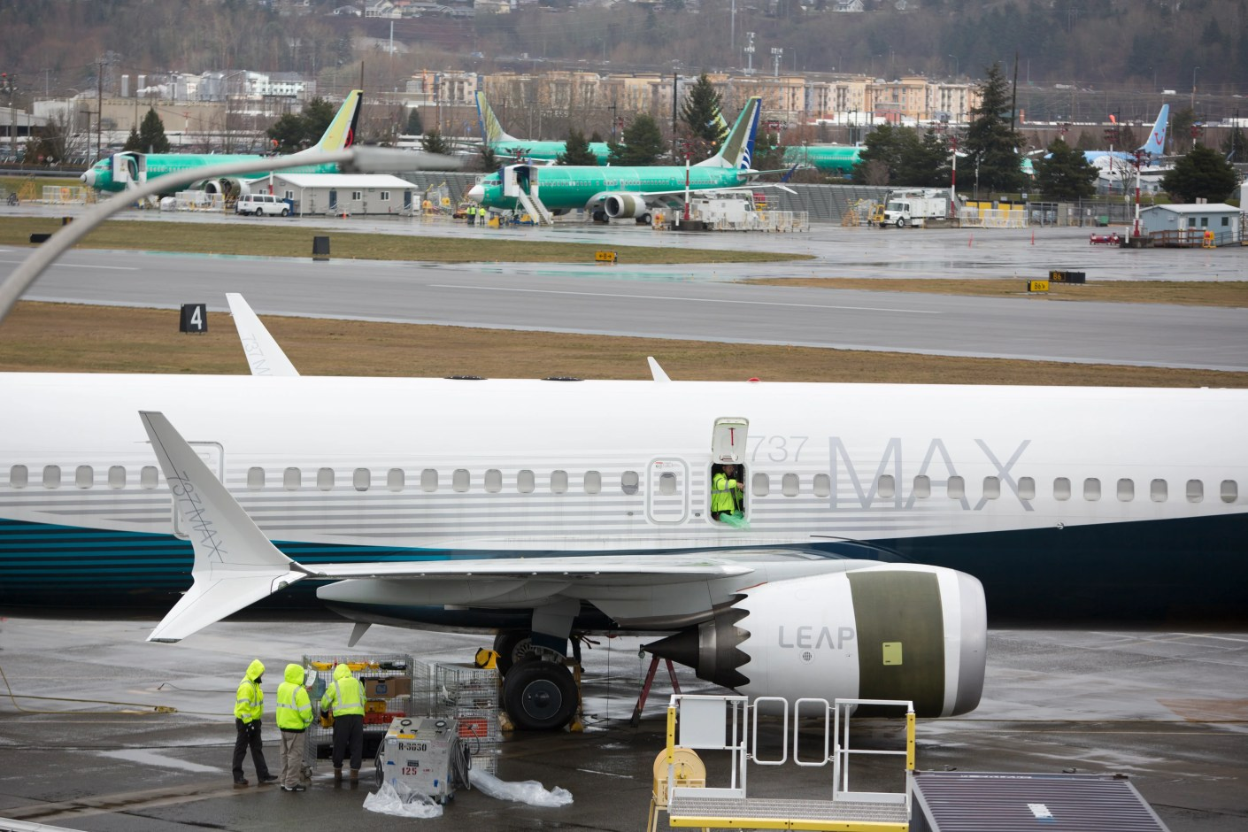 """Workers are pictured next to a Boeing 737 MAX 9 airplane on the tarmac at the Boeing Renton Factory in Renton, Washington on March 12, 2019. - US President Donald Trump on March 13, 2019, announced a plan to ground all Boeing 737 MAX aircraft amid intense international and political pressure following the second deadly crash in less than five months. """"We"""