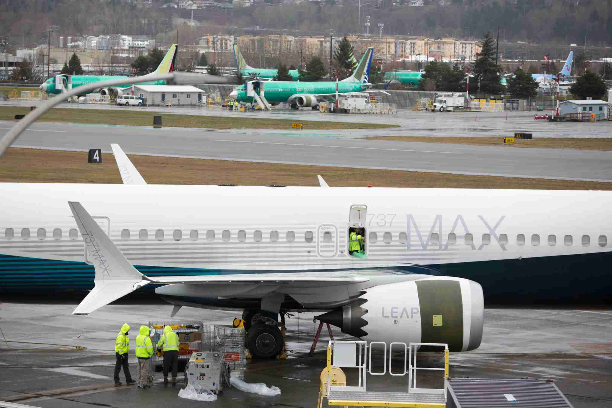 "Workers are pictured next to a Boeing 737 MAX 9 airplane on the tarmac at the Boeing Renton Factory in Renton, Washington on March 12, 2019. - US President Donald Trump on March 13, 2019, announced a plan to ground all Boeing 737 MAX aircraft amid intense international and political pressure following the second deadly crash in less than five months. ""We"