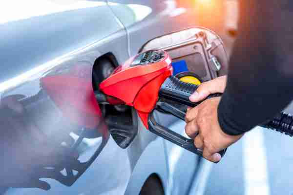 Gas pump, Oil station hand and fuel nozzle in car