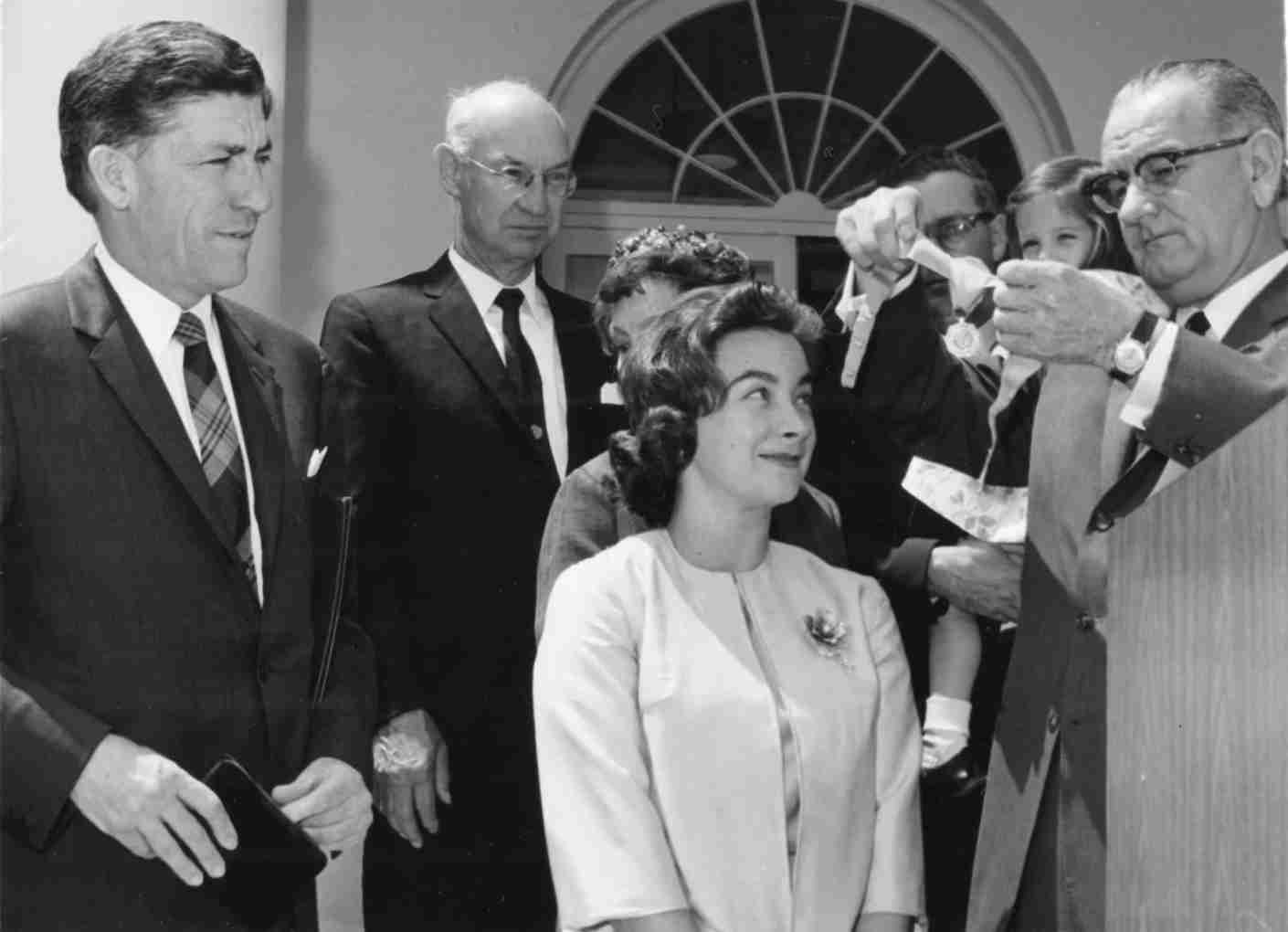 Outside the White House, American aviator Jerrie Mock (1925 - 2014) (center) smiles as US President Lyndon B Johnson presents her with an FAA award, Washington DC, May 4, 1964. The award was to commemorate Mock