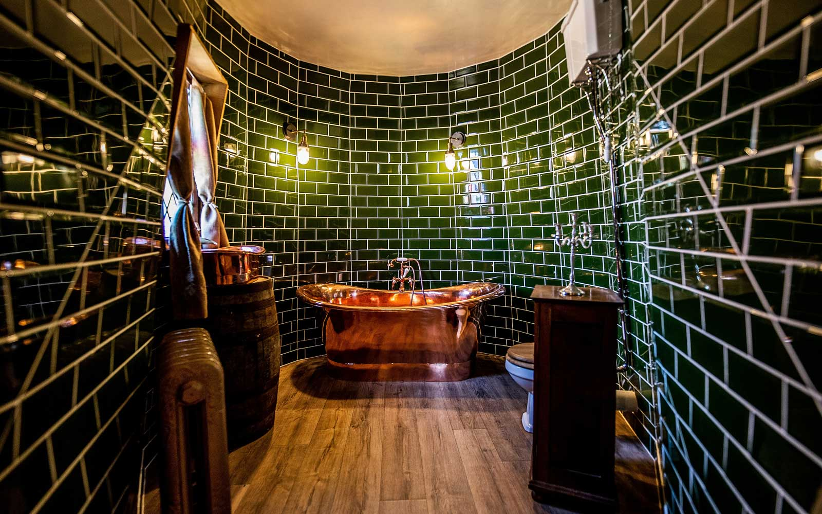 Picture Shows Bath Room Holiday home inspired by Harry PotterÕs HagridÕs Hut opens on the North York Moors Harry Potter fans can now rent a holiday cottage inspired by the fictional home of one of the booksÕ main characters, Rubeus Hagrid. The GroundkeeperÕs Cottage has just opened at North Shire near Saltburn on the edge of the North York Moors National Park, inspired by the film portrayal of HagridÕs Hut in the Harry Potter novels. The opening comes just ahead of International Harry Potter Day (2 May). The cottage comprises three interlocking circular slate-roofed buildings, two with turrets, and all with stained glass windows. Guests approach the lantern-lit wooden door before stepping into the spacious open plan living space comprising galley kitchen, dining area, seating in front of a feature fireplace and wood beams festooned with Hagrid-style paraphernalia such as old baskets, ropes, leather bags and lanterns. From the living room one door leads to the circular bedroom complete with double bed and a rustic wooden bunk bed, while a second door opens onto a large bathroom where the star feature is a huge freestanding copper bath. The owner Carol Cavendish, who has been a Harry Potter fan since her early 20s, has also incorporated small touches such as an ink bottle and quill and bespoke copper basin in the bathroom. However whereas Hagrid would have lived relatively frugally, guests staying in GroundkeeperÕs cottage wonÕt have to skimp on lifeÕs luxuries as two comfy sofas in the living room together with sleigh bed and high quality mattresses on the bunk bed make it more of a cosy, comfortable retreat. The cottage, which is available for rent from £195 per night, sleeps up to six (four in the bedroom and two on a sofabed). For those who want to bring their own Fang, one well-behaved dog is also allowed at a small extra cost. This is the next stage in North ShireÕs vision to create a storybook fantasy world for guests. Back in