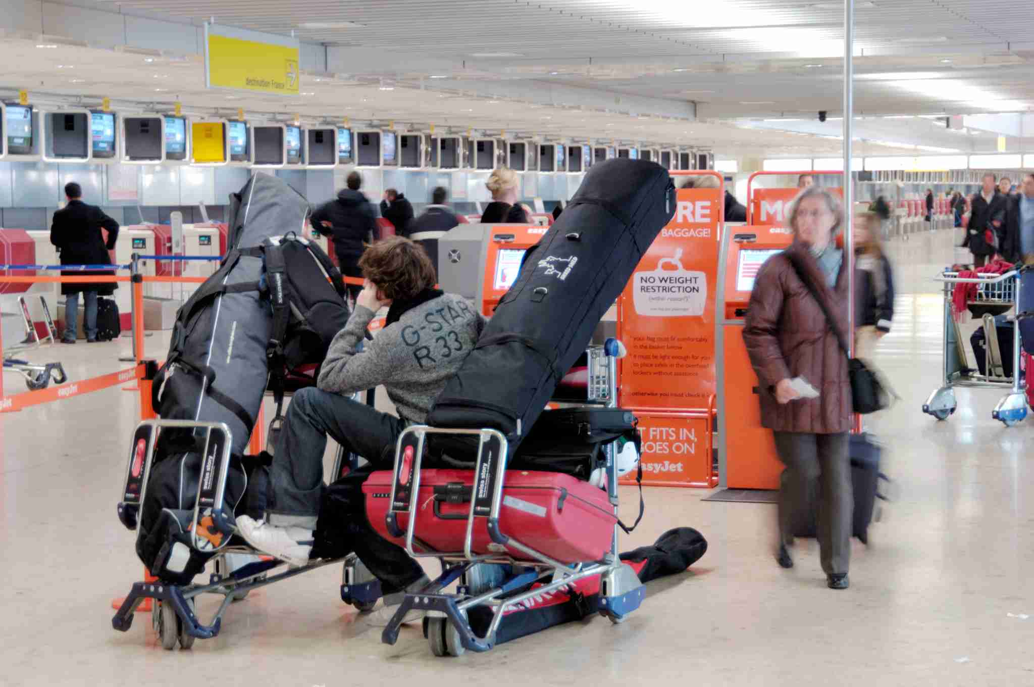 a man sitting on a baggage trolley full of luggage and skis in the easyJet check-in area. (Photo by: aviation-images.com/UIG via Getty Images)