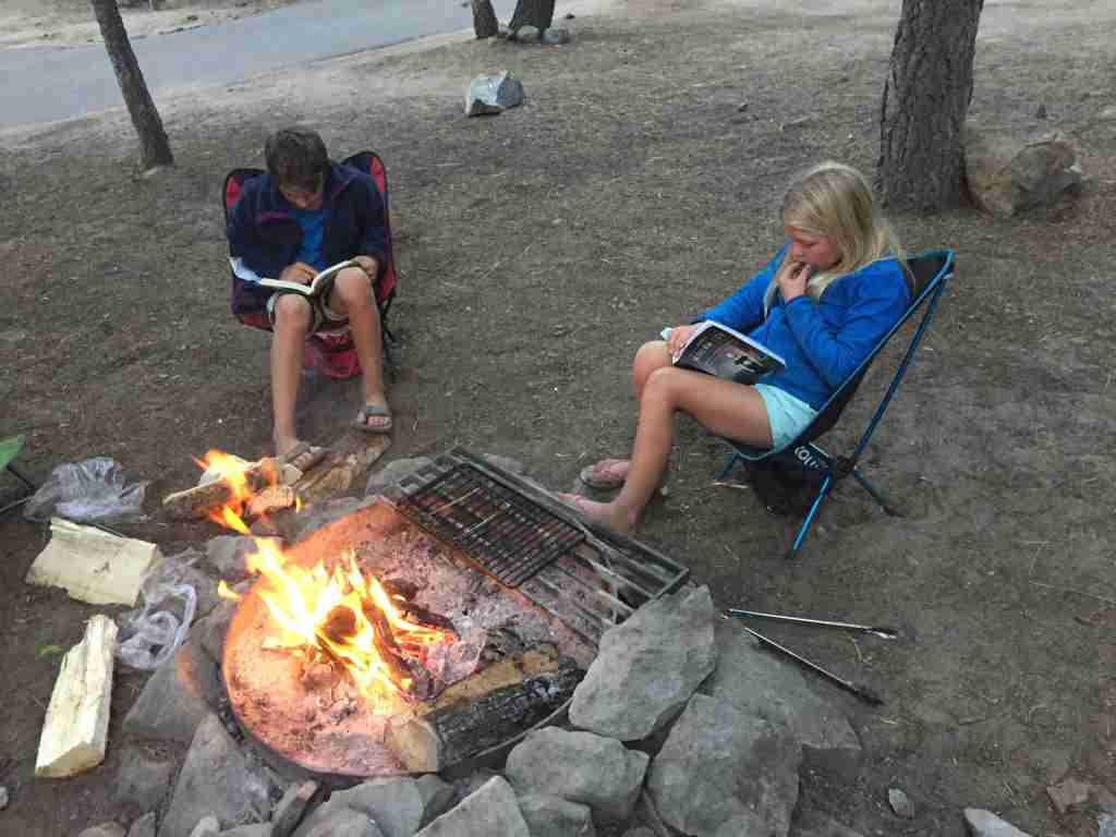 Kids reading around a campfire at Yellowstone.