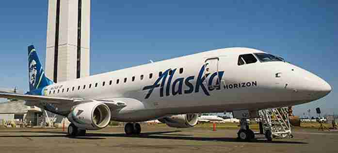 A Horizon Air Embraer E175 jet painted in Alaska Airlines colors sits near the control tower at Paine Field in Everett, Washington. (Courtesy of Alaska Airlines)