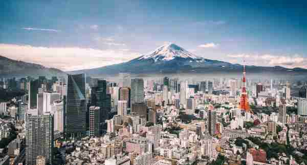 View of Mt. Fuji, Tokyo Tower and crowded buildings in downtown Tokyo.