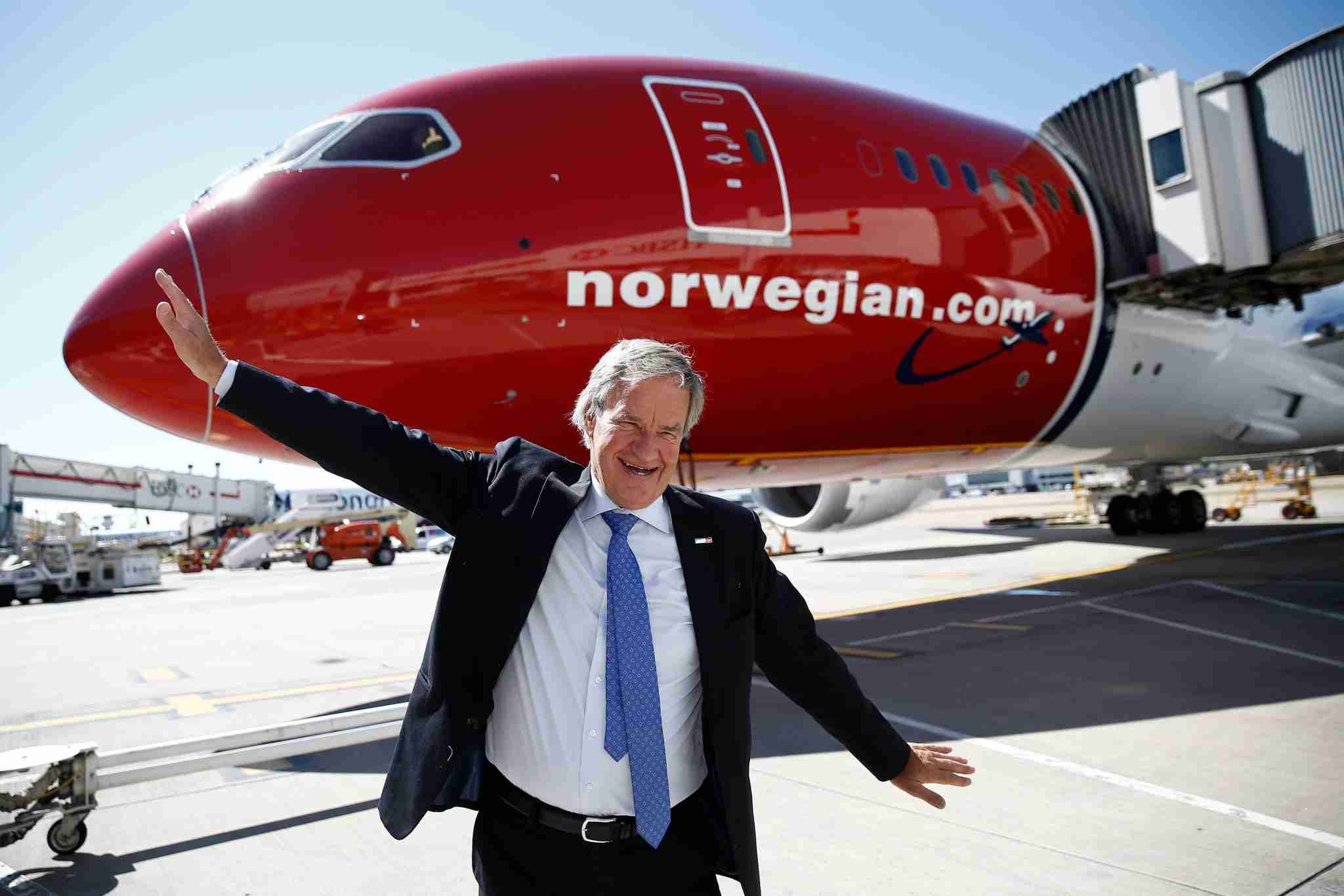 Norwegian Air CEO Bjørn Kjos poses for a photograph with his arms outstretched in front of a Boeing 787 Dreamliner ahead of the company