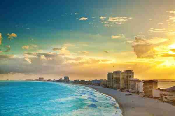 Subject: A panoramic view of the hotel district of Cancun at sunset. A popular tourist beach destination. The Yucatan Peninsula and the Riviera Maya in Mexico is a well developed vacation location with numerous hotels and entertainment districts. (Image by YinYang/iStock / Getty Images Plus)