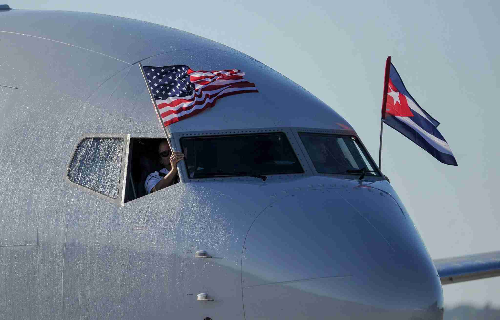 An American Airlines plane fluttering U.S. and Cuban flags is seen upon arrival at Jose Marti International Airport on Nov. 28, 2016, becoming the first Miami-Havana commercial flight in 50 years. (Photo by Yamil Lage/AFP via Getty Images)