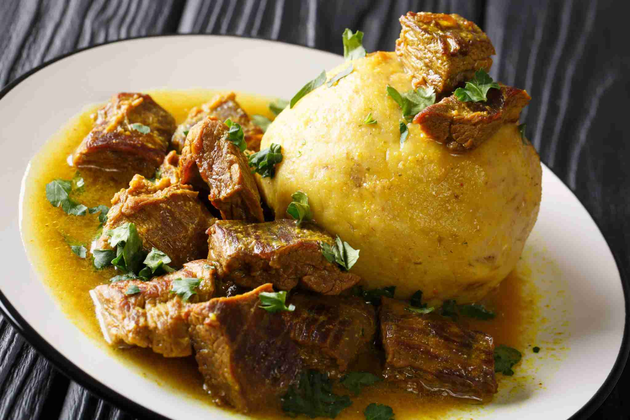 Puerto Rican Mofongo made from plantains, garlic and chicharron served with meat and broth close-up on a plate on the table. horizontal