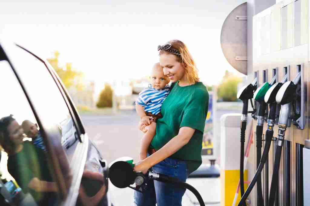 mother and baby at gas pump