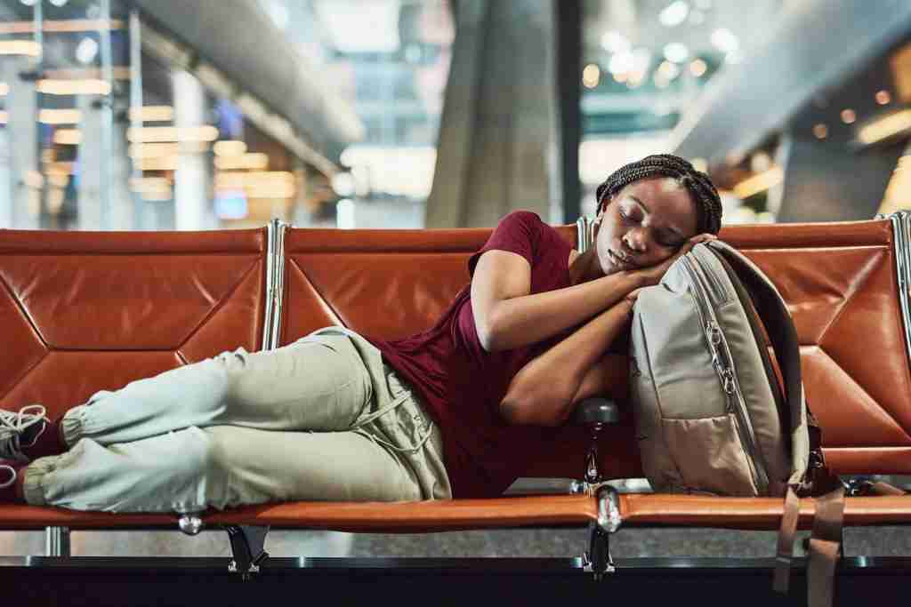 Shot of a young woman falling asleep at the airport while waiting for departure