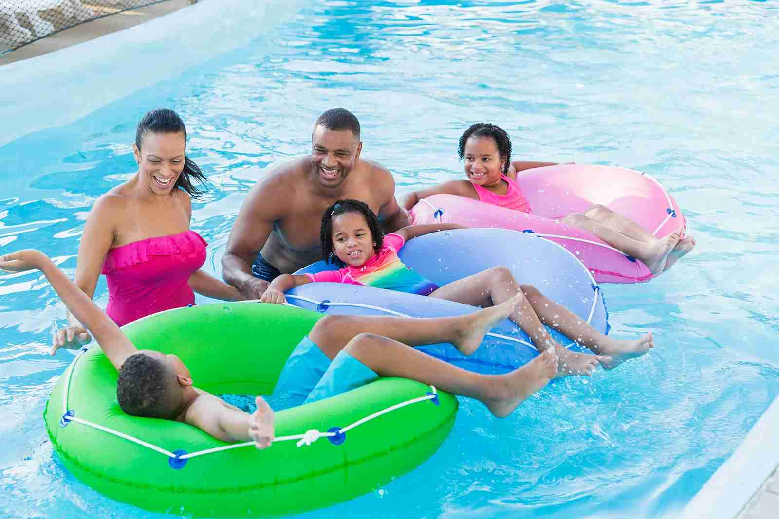 A large mixed race family with three children having fun at a water park on the lazy river. The parents are standing in the water and the two girls and a boy are lying on inflatable innertubes.