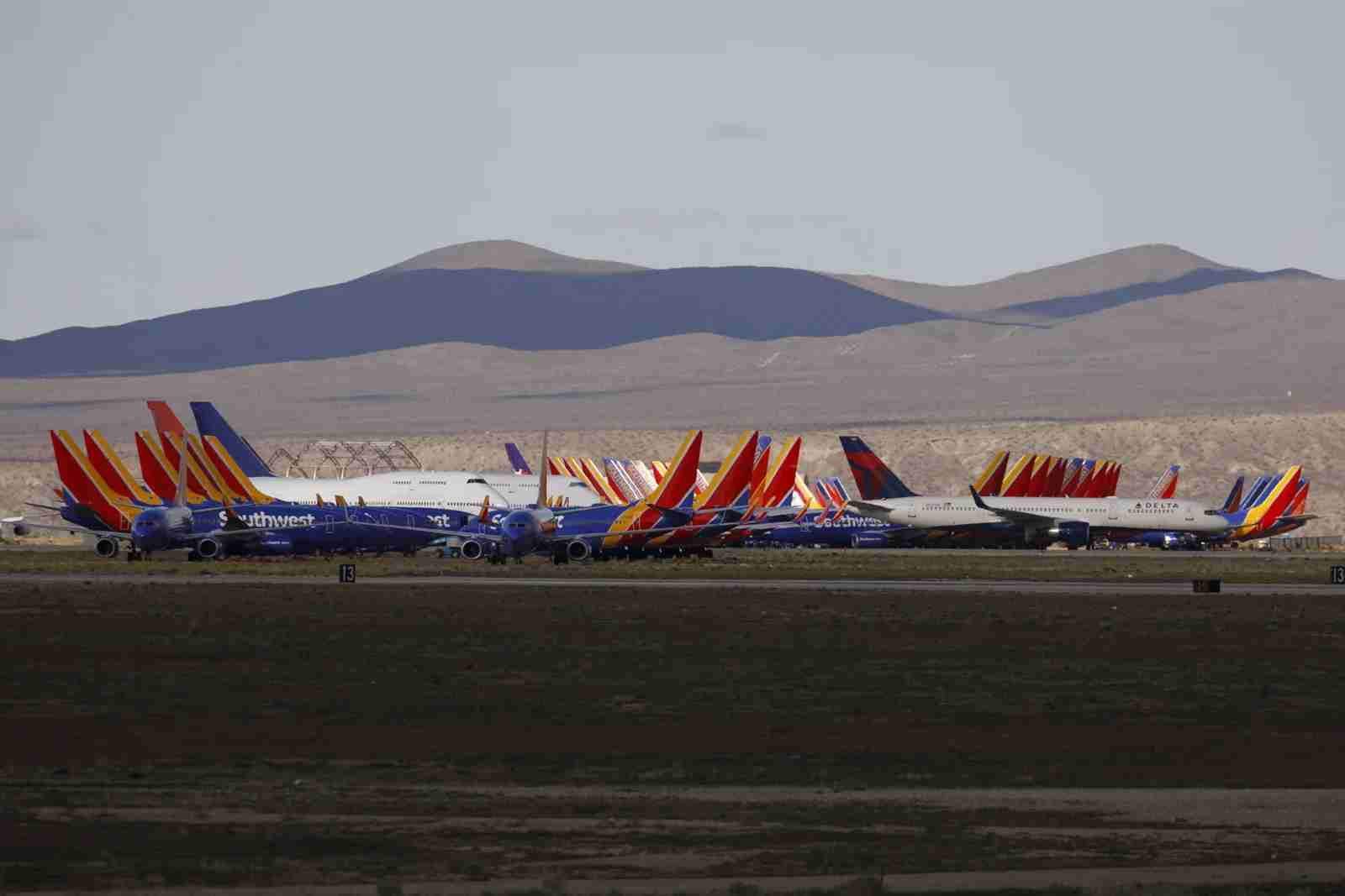A Delta Air Lines Inc. aircraft, center right, taxis past Southwest Airlines Co. planes parked at a field in Victorville, California, U.S., on Monday, March 23, 2020. Southwest, which carries the most passengers in domestic markets, said it will cut 1,000 daily flights starting Sunday, ahead of a previously planned 20% capacity reduction, because of a rapid drop in near-term demand. (Photo by Patrick T. Fallon/Bloomberg/Getty Images)