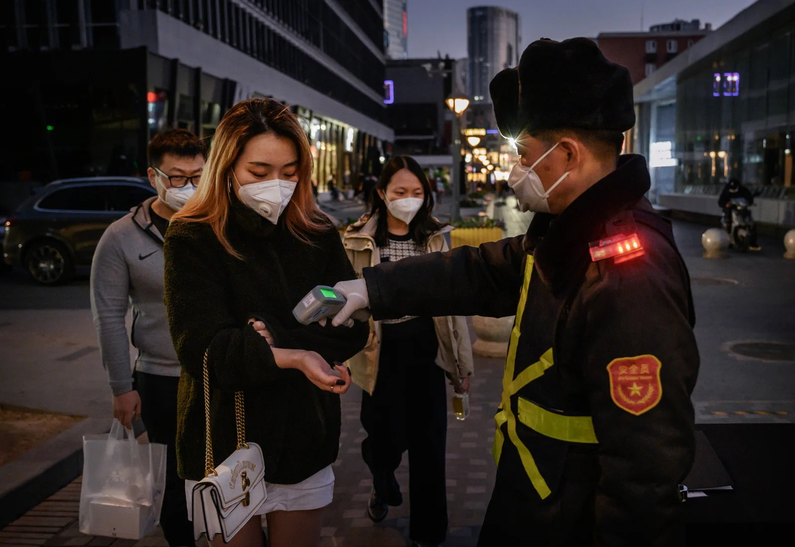 A Chinese woman wears a protective mask as she has her temperature checked by a security guard. (Photo by Kevin Frayer/Getty Images)