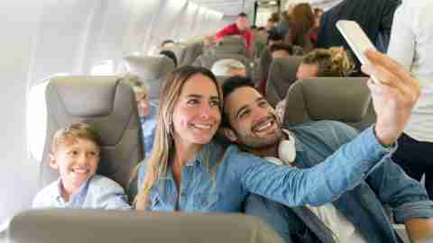family taking selfie on airplane