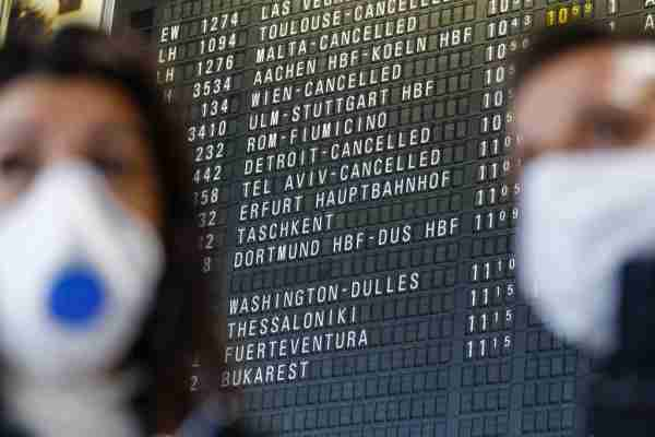 Travelers wear face masks near a flight departure information board showing a cancelled flight to Detroit at Frankfurt Airport, operated by Fraport AG, in Frankfurt, Germany, on Thursday, March 12, 2020. President Donald Trumps 30-day ban on Europeans traveling to the U.S. delivers a hammer blow to a global airline industry that was already at risk of losing as much as $113 billion in passenger revenue this year because of the coronavirus. Photographer: Alex Kraus/Bloomberg via Getty Images