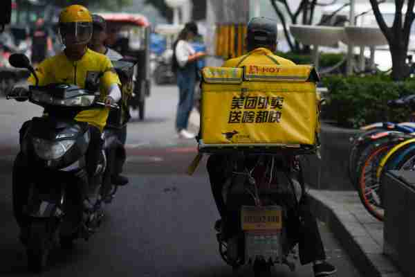 Two Meituan food deliverymen ride their scooters in Beijing on June 26, 2018. - Chinese online services giant Meituan-Dianping filed for an initial public offering in Hong Kong on June 25 in what could become the biggest IPO of the year. (Photo by WANG ZHAO / AFP) (Photo credit should read WANG ZHAO/AFP via Getty Images)