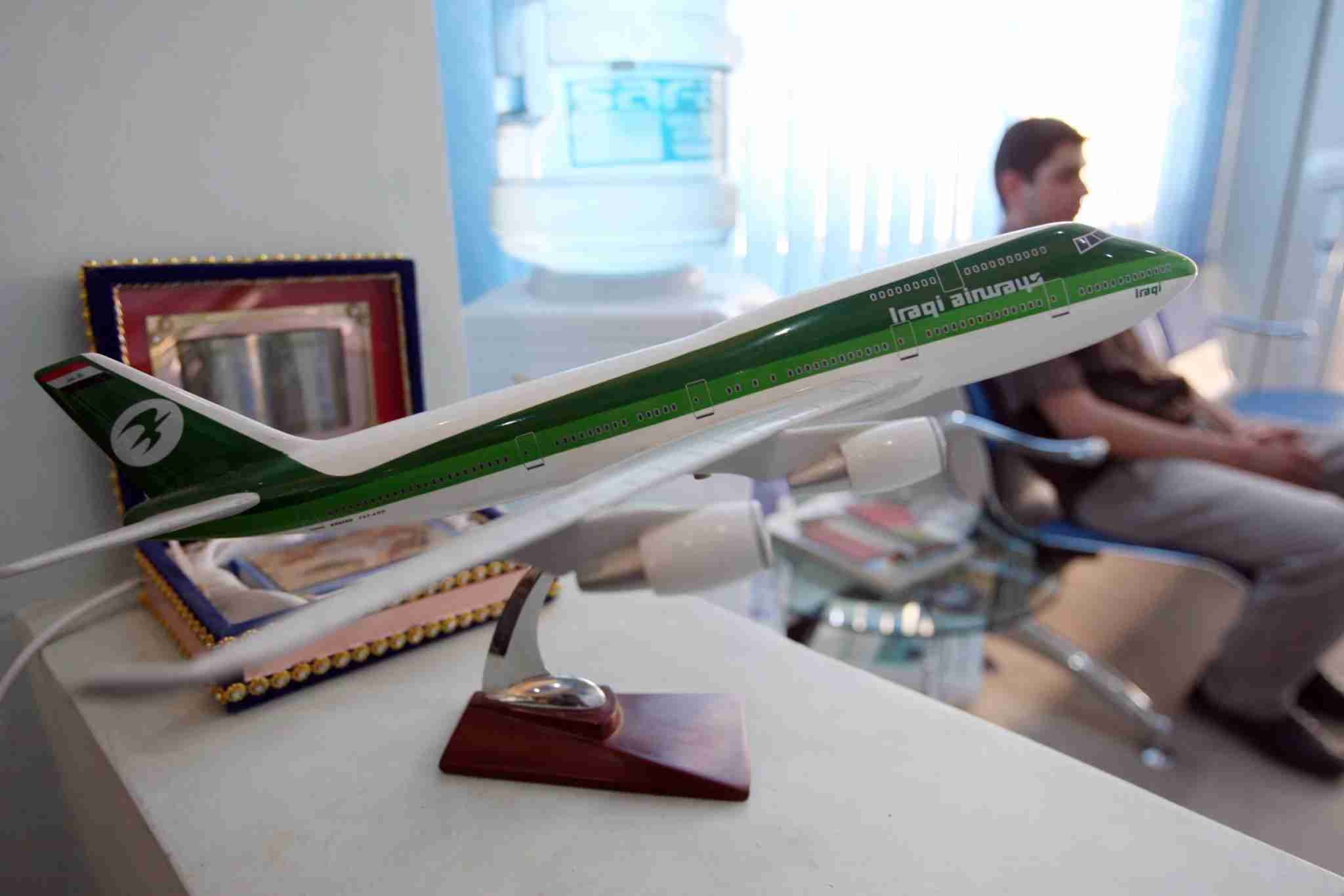 A model plane sits on a desk as customers wait at an Iraqi Airways office in Baghdad on May 26, 2010. Baghdad has decided to close down state-owned Iraqi Airways in the face of a decades-old financial dispute with neighbouring Kuwait that prompted the seizure of one of its aircraft last month, the transport ministry has announced. AFP PHOTO/ALI AL-SAADI (Photo credit should read ALI AL-SAADI/AFP via Getty Images)