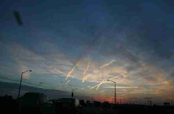 Jet contrails rise above the traffic on the Belt Parkway. (Photo by Andrew Lichtenstein/Corbis via Getty Images)