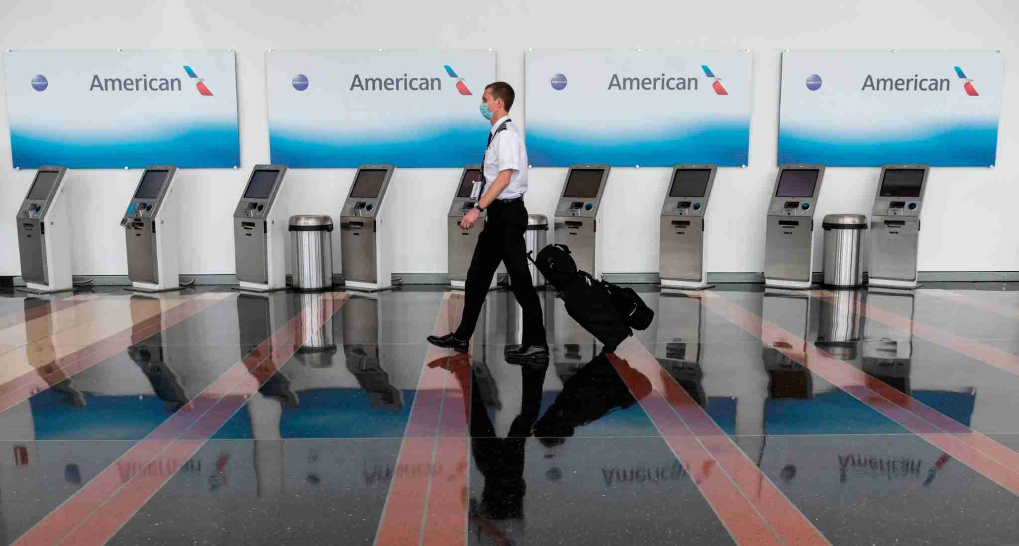 An airline employee walks past empty American Airlines check-in terminals at Ronald Reagan Washington National Airport in Arlington, Virginia, on May 12, 2020. - The airline industry has been hit hard by the COVID-19 pandemic, with the number of people flying having decreased by more than 90 percent since the beginning of March. (Photo by ANDREW CABALLERO-REYNOLDS / AFP) (Photo by ANDREW CABALLERO-REYNOLDS/AFP via Getty Images)