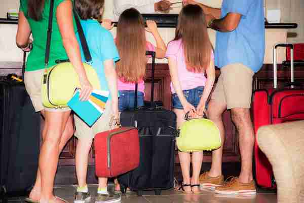 Multi-ethnic family on summer vacation checks into their hotel. They are carring suitcases, luggage, and travel brochures with them.  The family of five has three elementary-age children and two parents. Latin and caucasian ethnicities.  They are ready for vacation. Tourism, travel themes.