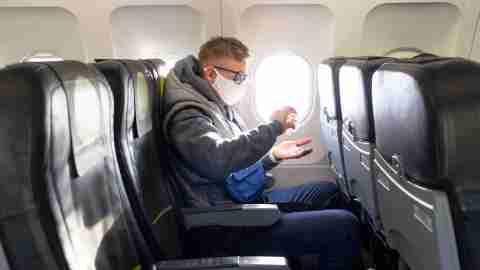 Man on plane wearing face mask