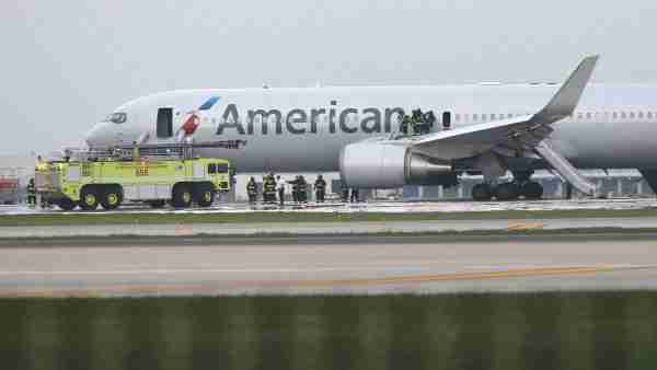 Firefighters extinguish flames from American Airlines Flight 383, bound for Miami, which caught fire on a runway at O'Hare International Airport in Chicago on Friday, Oct. 28, 2016. (Antonio Perez/Chicago Tribune/TNS via Getty Images)