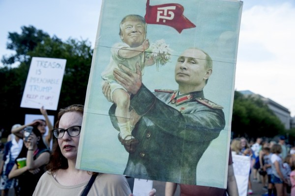 A woman holds a sign depicting Russian President Vladimir Putin and President Donald Trump during a protest outside the White House, Tuesday, July 17, 2018, in Washington. This is the second day in a row the group has held a protest following President Donald Trump's meetings with Russian President Vladimir Putin. (AP Photo/Andrew Harnik)