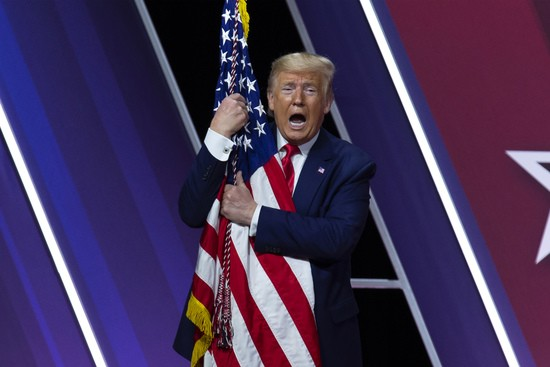 President Donald Trump hugs and kisses the American flag after speaking at Conservative Political Action Conference, CPAC 2020, at the National Harbor, in Oxon Hill, Md., Saturday, Feb. 29, 2020. (AP Photo/Jose Luis Magana