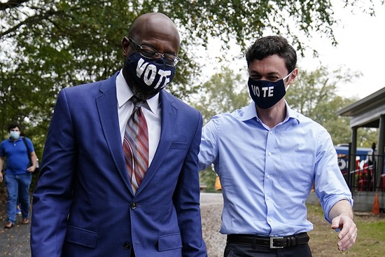 """Democratic candidate for Senate Jon Ossoff, right, and Democratic candidate for Senate Raphael G Warnock, left, arrive before they speak to a crowd during a """"Get Out the Early Vote"""" event at the SluttyVegan ATL restaurant on Tuesday, Oct. 27, 2020, in Jonesboro, Ga. (AP Photo/Brynn Anderson)"""