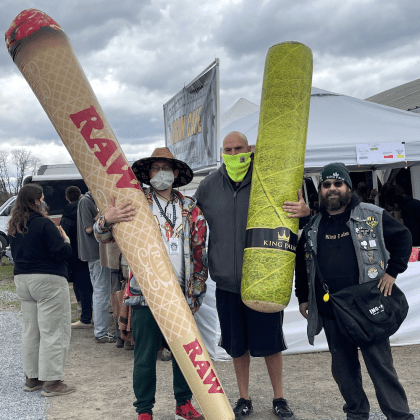 John Fetterman stands next to cannabis enthusiasts holding inflatable joints.