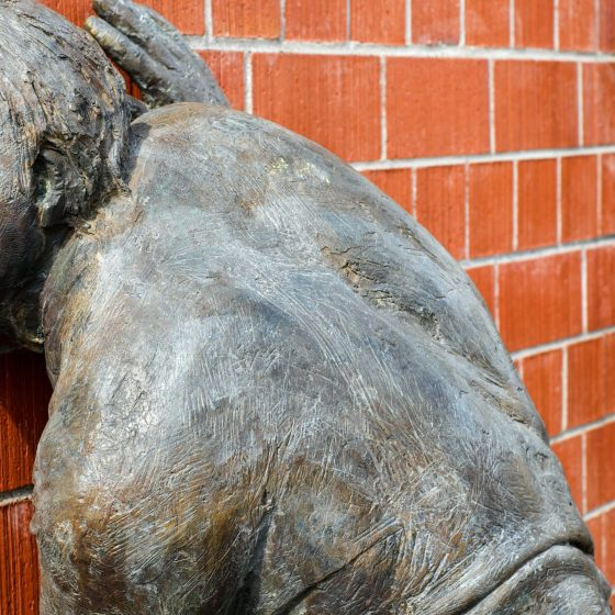 Sculpture of two bronze men listening at a wall