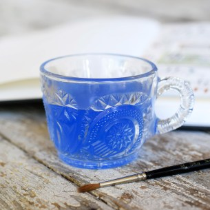 This pressed glass art water cup features a delightful floral pattern!