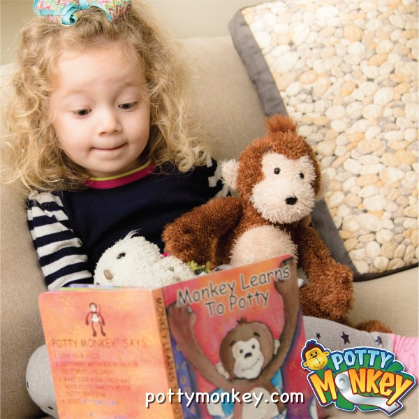 Young child reading the Monkey Learns to Potty Book with potty monkey doll beside her.