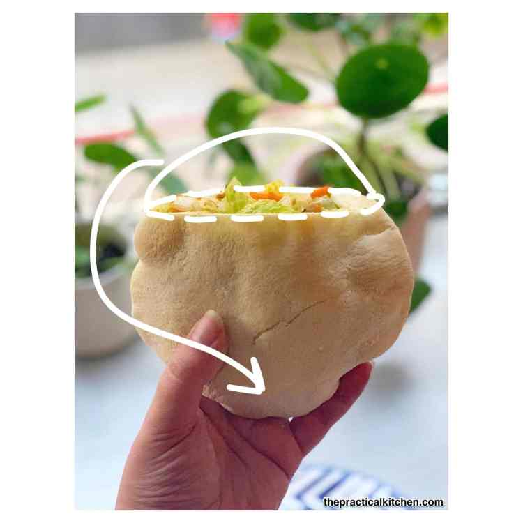 a hand holds up a pita pocket sandwich. the top quarter of the pocket has been removed and lettuce and carrots are sticking out the top. drawn on top of the image is an outline of where the top of the pita used to be and an arrow pointing to the bottom of the pita pocket.