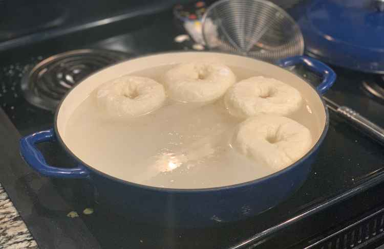 Four shaped bagels float in boiling water. They're in a wide, flat royal blue cast-iron enameled braising dish with a white interior. A metal wire spider and the lid to the pot sit on the stovetop to the right.