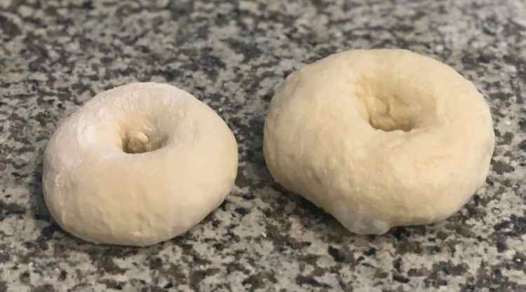 Two bagels sit side-by-side. The smaller one, on the left, still has a light dusting of flour on it and hasn't been boiled yet. The bigger one is on the right and has a lightly dimpled texture from being boiled. They're sitting on a gray quartz counter top.