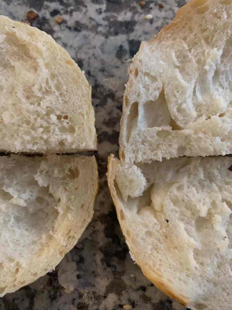 Close up comparing the crumb and crust of two sliced open bagels. The one on the left is slightly smaller and has a thinner crust. The one on the right is larger and has a thicker crust.