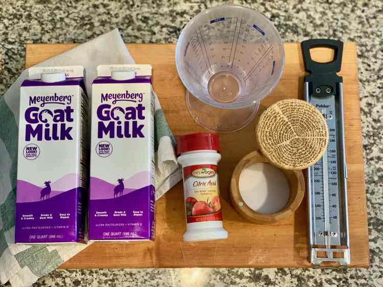 An overhead view of a large wooden cutting board. On the left side of the cutting board are two one-quart containers of Meyenberg ultra-pasteurized Goat Milk on top of a clean white and green dish towel. In the top middle of the board is a clear conical liquid measuing cup filled with a quarter-cup of water. The bottom middle of the board has a red and white bottle of citric acid, a wooden container filled with salt. On the right side of the cutting board is a silver candy thermometer with a black handle at the top.