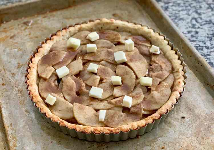 Small cubes of butter dot the top of a golden brown pre-baked tart shell filled with thin slices of pear arranged in loosely concentric circles and coated with a brown sugar mixture. The tart pan sits on a sheet tray.