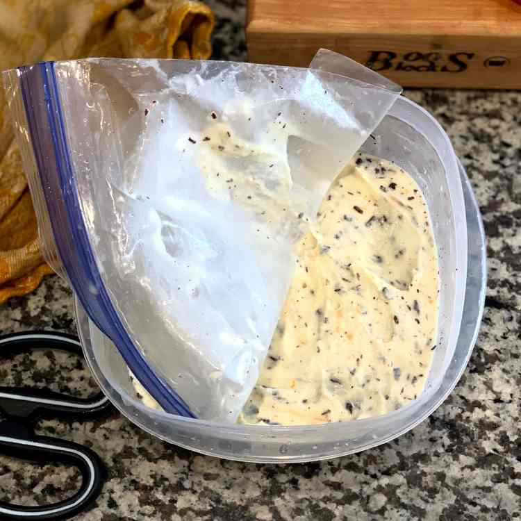 A light yellow ice cream flecked with dark slivers of chocolate sits in a square tupperware. A plastic ziplock bag is pressed against the surface of the ice cream, with half of it peeled back to reveal the ice cream. A pair of scissors sits to the left and the edge of a Boos block peeks into the top right corner.