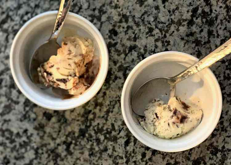 Two white ceramic ramekins sit on a grey speckled countertop. Each ramekin has a scoop of orange-cardamom ice cream with chocolate chips and a hot fudge swirl. There is a spoon in each cup.